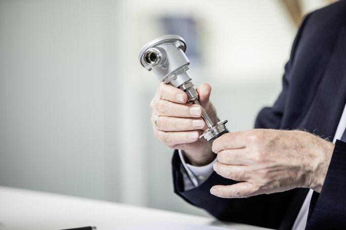 Hände mit JUMO Einschraub-Widerstandsthermometer